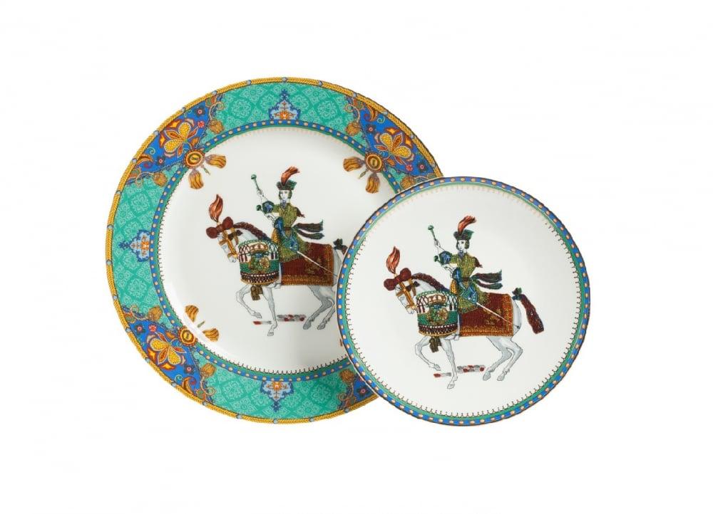 Комплект тарелок Jinete DG-HOME Комплект тарелок Jinete выполнен из костяного  фарфора. Большая тарелка расписана ярким  орнаментом по всему краю, с элементами геральдической  символики. По краю меньшей тарелки нанесена  узкая полоска орнамента. На дне тарелок  изображена воинственная наездница. Единство  символики рисунка и формы составляют выразительную  композицию. Подойдет к многим стилям сервировки.