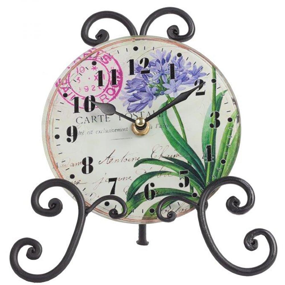 Часы на подставке LiliaЧасы<br>Роскошный интерьер складывается из деталей. <br>Часы на подставке Lilia — это тот элемент <br>декора, который непременно привнесет в <br>ваш дом дополнительный уют, красоту и изысканность. <br>Необычное сочетание стеклянного циферблата <br>и кованой металлической подставки дает <br>поистине оригинальный аксессуар. Растительные <br>мотивы, украшающие часы, будут отлично гармонировать <br>с общей картиной помещения, оформленного <br>в любом стиле.<br><br>Цвет: Разноцветный<br>Материал: Стекло, Металл, Часовой механизм<br>Вес кг: 0,3<br>Длина см: 20,5<br>Ширина см: 21,5<br>Высота см: 9,5