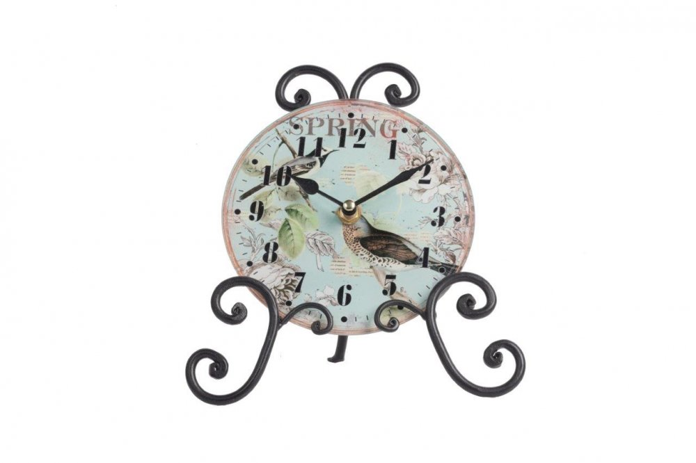 Часы на подставке FliegenЧасы<br>Роскошный интерьер складывается из деталей. <br>Часы на подставке Fliegen — это тот элемент <br>декора, который непременно привнесет в <br>ваш дом дополнительный уют, красоту и изысканность. <br>Необычное сочетание стеклянного циферблата <br>и кованой металлической подставки дает <br>поистине оригинальный аксессуар. Растительные <br>мотивы, украшающие часы, будут отлично гармонировать <br>с общей картиной помещения, оформленного <br>в любом стиле.<br><br>Цвет: Разноцветный<br>Материал: Стекло, Металл, Часовой механизм<br>Вес кг: 0,3<br>Длина см: 20,5<br>Ширина см: 21,5<br>Высота см: 9,6