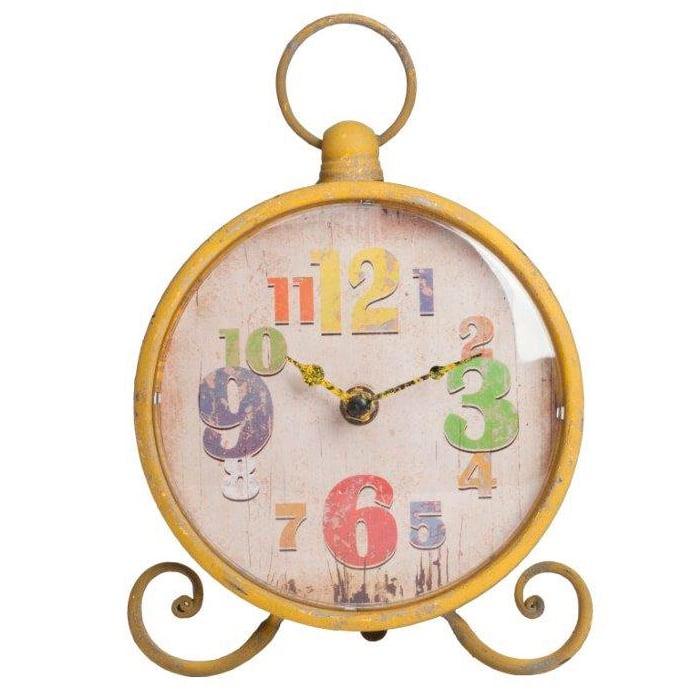 Настольные часы Lumiere YellowЧасы<br>Настольные часы Lumiere Yellow — круглой формы <br>на ножках, в виде завитков, сверху вмонтировано <br>кольцо, имеют оригинальный вид. Благодаря <br>жёлтому, немного состаренному, корпусу <br>и оригинальному декору циферблата, в виде <br>разных по величине и цвету цифр, забавный <br>аксессуар непременно впишется в общую картину <br>помещения и будет вызывать улыбку. Выберите <br>часы из коллекции Lumiere любого из четырех <br>цветов — голубого, оранжевого, жёлтого, <br>зелёного.<br><br>Цвет: Жёлтый<br>Материал: Металл, Пластик<br>Вес кг: 0,3<br>Длина см: 17,78<br>Ширина см: 16,51<br>Высота см: 22,86
