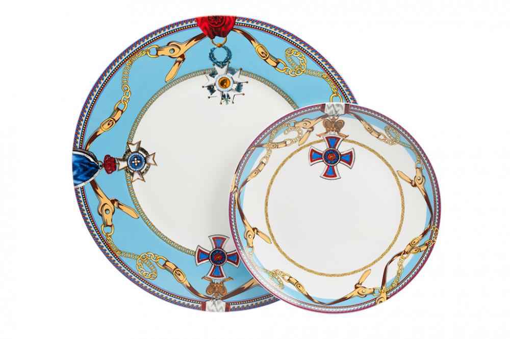 Комплект тарелок Courage DG-HOME Комплект тарелок Courage II выполнен из костяного  фарфора. Большая тарелка расписана ярким  орнаментом по голубому фону, с элементами  геральдической символики. По краю меньшей  тарелки нанесена узкая полоска орнамента.  Сочетание символики рисунка и формы составляют  выразительную композицию. Подойдет к многим  стилям сервировки.