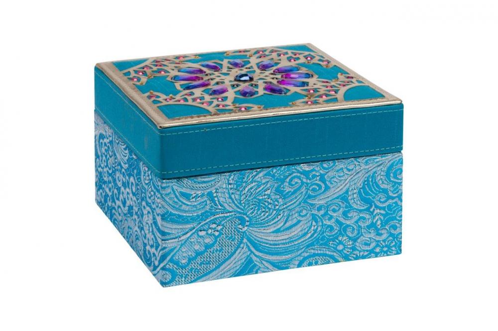 Декоративная шкатулка Blossom BlueШкатулки и подставки для украшений<br>Декоративная шкатулка Blossom изготовлена <br>из дерева, покрыта голубой тканью с рисунком. <br>Крышка шкатулки инкрустирована камнями <br>фиолетового цвета в восточном стиле. По <br>периметру крышки — окаймление золотого <br>цвета. Поверхность крышки придаёт шкатулке <br>дорогой и оригинальный вид. Приобретите <br>шкатулку в качестве подарка.<br><br>Цвет: Голубой, Фиолетовый, Золото<br>Материал: Дерево, Ткань<br>Вес кг: 0,4<br>Длина см: 15<br>Ширина см: 15<br>Высота см: 10