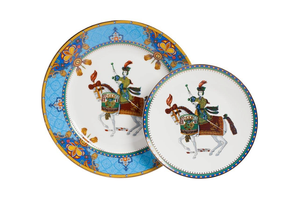 Комплект тарелок Jinete Twin DG-HOME Комплект тарелок Jinete выполнен из костяного  фарфора. Большая тарелка расписана ярким  орнаментом по голубому фону, с элементами  геральдической символики. По краю меньшей  тарелки нанесена узкая полоска орнамента.  На дне тарелок изображена воинственная  наездница. Сочетание символики рисунка  и формы составляют выразительную композицию.  Подойдет к многим стилям сервировки.